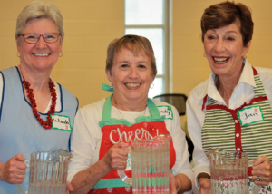 Three women smiling into the camera holding pitchers of water