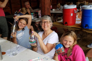 One woman and two girls paint glass bottles